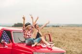 Fényképek gyönyörű fiatal barátnői, autó fejkötő emelt kézzel ül, és a béke tüneteit mutató