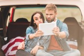 Fotografie beautiful young couple making selfie with tablet while sitting in car trunk during trip