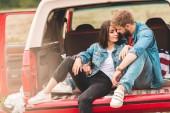 gyönyörű fiatal pár hozzábújva az autó törzs út során
