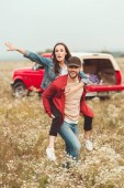 happy young woman piggybacking on boyfriend in flower field with blurred car on background