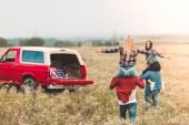 Junge Frauen bei Autofahrt auf Schultern von Freunden im Feld