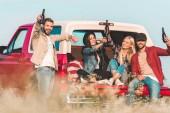 Gruppe von jungen Leuten mit Flaschen Bier beim Sitzen im Kofferraum eines Autos Toasten