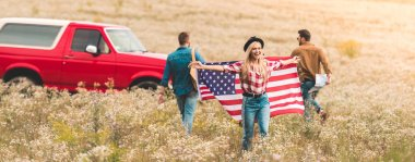 group of young friends with united states flag in flower field during road trip