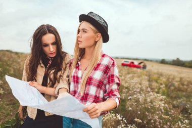 confused young girlfriends with map standing in field and trying to navigate