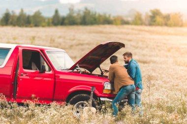 handsome young men looking at broken car engine in field