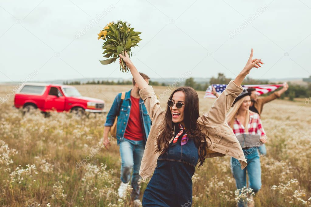 happy young woman holding bouquet and walking by field with friends during trip