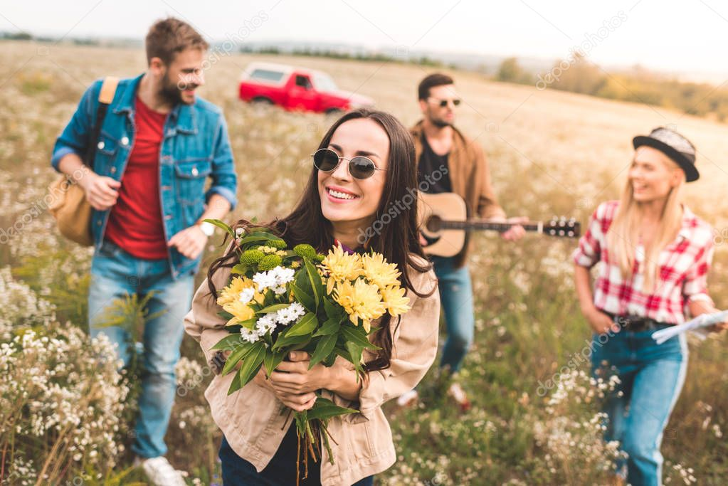group of young people walking by field with guitar and flower bouquet
