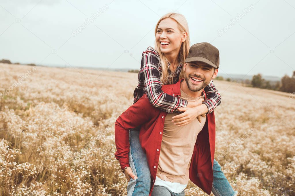 happy young woman piggybacking on boyfriend in flower field