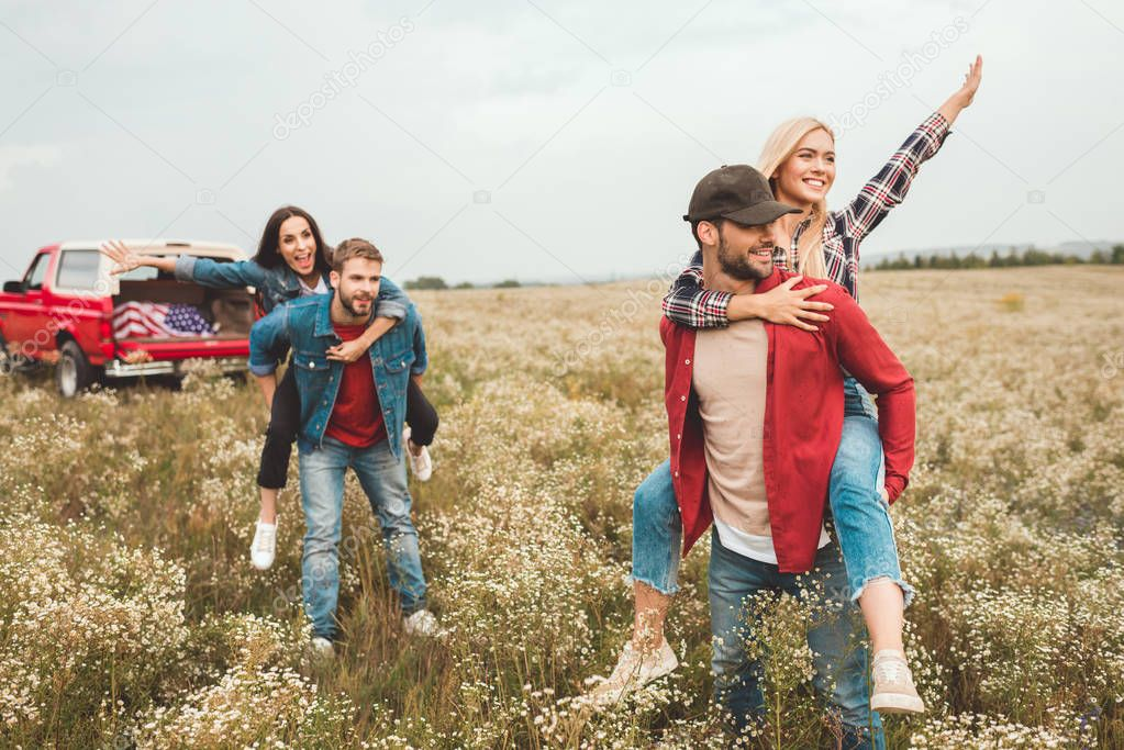 young happy women piggybacking on boyfriends and waving in flower field during car trip
