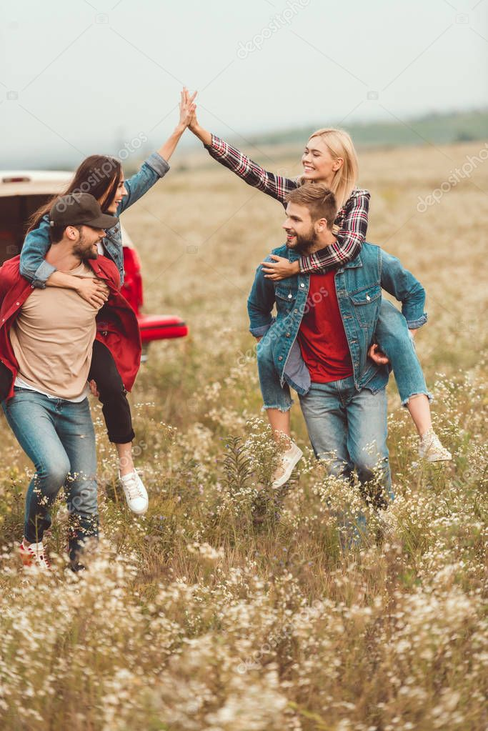young women piggybacking on boyfriends and giving high five in flower field