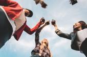 Blick von unten auf eine Gruppe junger Leute, die vor wolkenverhangenem Himmel Bierflaschen klappern