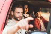 schöner junger Mann zeigt irgendwo hin, während er mit Freunden Auto fährt