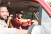 Happy mladí přátelé cestování autem a na koni polem květina
