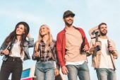 Blick von unten auf eine Gruppe fröhlicher junger Leute mit Bierflaschen und Gitarre, die durch das Feld laufen