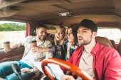 Gruppe junger Leute plant Autofahrt und freut sich
