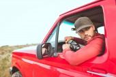 pohledný mladý muž jízdy staré červené auto v poli a při pohledu zpět