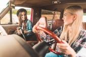 šťastné mladé kamarádky s autem a chatování v autě