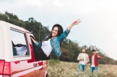 young woman outstretching from car window and raising hand while men standing blurred on background in flower field