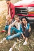 Gruppe fröhlicher junger Autofahrer sitzt auf Blumenfeld und lehnt sich auf Oldtimer-LKW zurück
