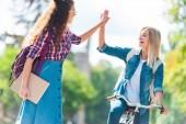 Fotografie spokojenými studenty dávat vysoké pět navzájem v parku