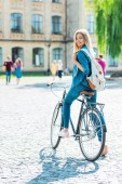Fotografie selective focus smiling young student with backpack on bicycle looking at camera on street