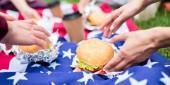 částečný pohled přátel s hamburgery a americká vlajka na zelené trávě v parku