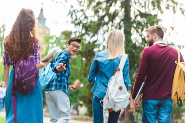 selective focus of multicultural students with backpacks walking on street