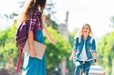 happy student looking at classmate while riding bicycle on street
