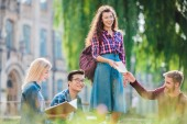 Fotografie multiracial students studying in park with university on background