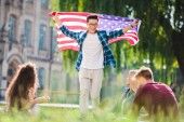 Fotografie multicultural students with american flag in summer park