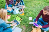 Fotografie partial view of multiethnic students with notebooks and digital devices sitting on green grass in park