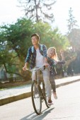 Happy mnohonárodnostní studenti dohromady jezdit kole na ulici