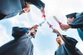 Fotografie bottom view of multiracial graduates with diplomas in hands and blue sky on background
