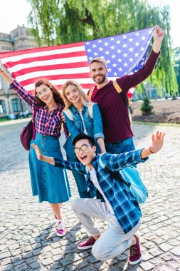smiling multicultural students with american flag in park