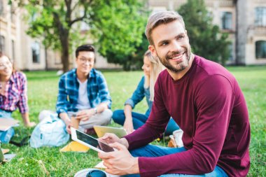 multiracial smiling students with digital devices sitting on green grass in park