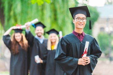 selective focus of smiling asian graduate with classmates behind in summer park