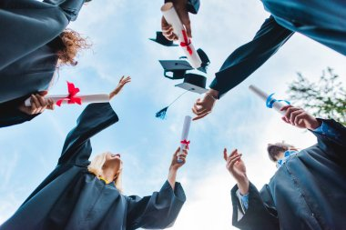 bottom view of happy multicultural graduates with diplomas throwing caps up with blue sky on background