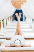 Fotografie girl lying on sun lounger in white shoes and hat