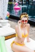 usmívající se atraktivní dívka v plavkách sedí na lehátku a při pohledu na fotoaparát nad sluneční brýle