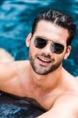krásný usměvavý muž v sluneční brýle při pohledu na fotoaparát blízko u bazénu