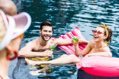 smiling friends with cocktails and inflatable mattress resting in swimming pool