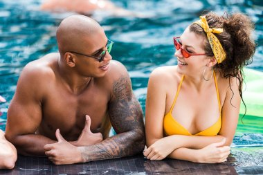 young in sunglasses looking at each other in swimming pool