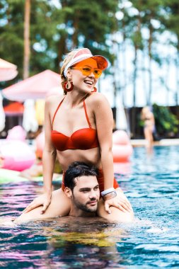 smiling woman in red swimsuit looking away while sitting on boyfriends shoulders in swimming pool