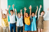 Fotografie adorable happy schoolchildren with raised hands standing in front of blank chalkboard