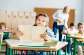 roztomilá malá školačka čtení knihy během lekce