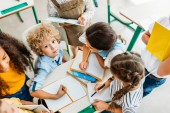 high angle view of schoolchildren writing off homework of their classmate during break