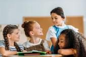 Fotografie Schulmädchen im Chat mit ihren Klassenkameraden während Pause im Klassenzimmer