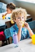 entzückender lockiger Schuljunge beim gemeinsamen Mittagessen in der Schulmensa