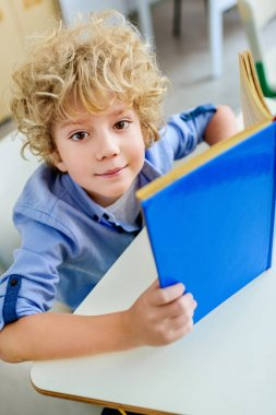 close-up portrait of adorable curly schoolboy with book looking at camera