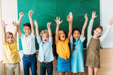 adorable happy schoolchildren with raised hands standing in front of blank chalkboard